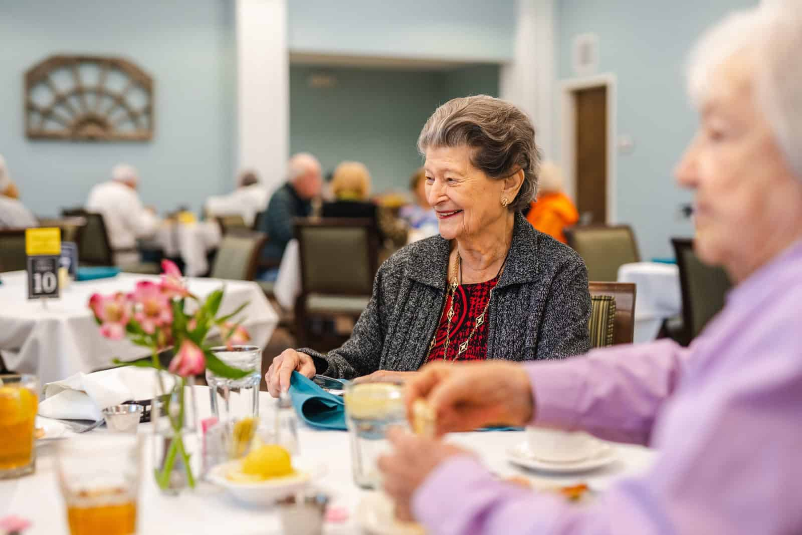 Smiling Senior Women Seated At Dining Table In Community Dining Room