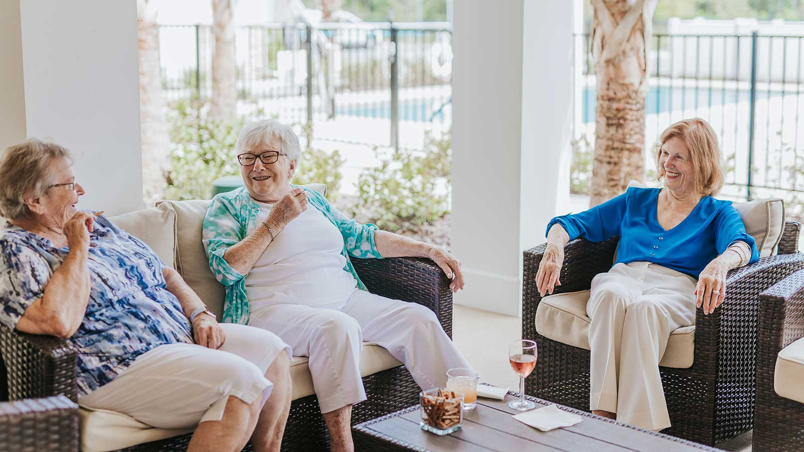 Staff member sitting with two senior women on independent living community patio with pool visible in background