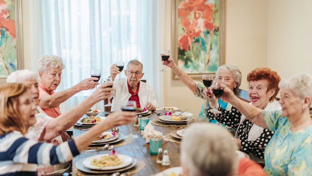 Senior men and women seated in independent living community private dining room toasting wine glasses